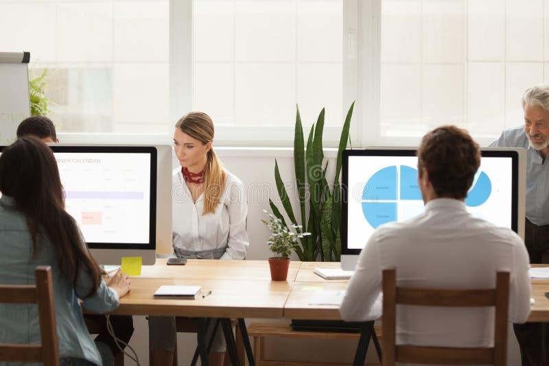 Affärsfolk som arbetar på datorer som delar kontorsskrivbordet i cowo royaltyfri fotografi