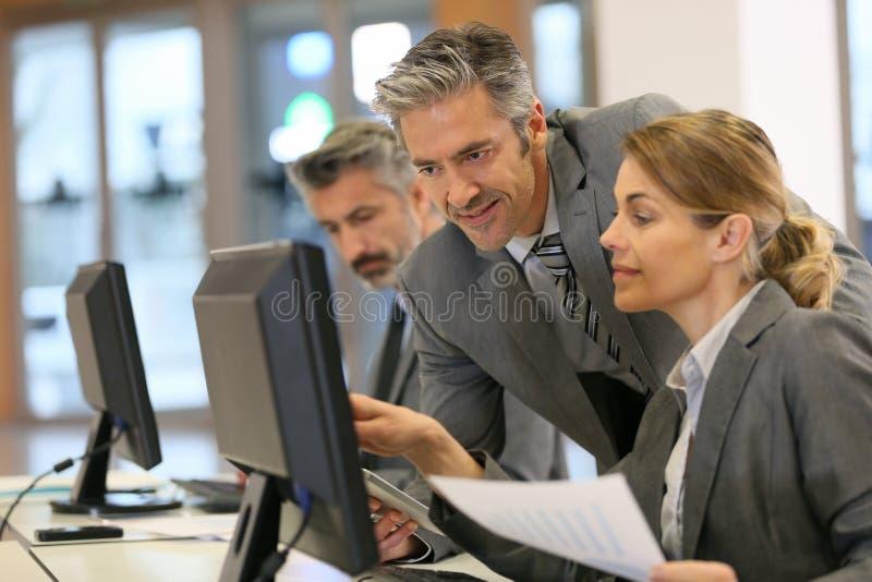 Affärsfolk som arbetar på kontoret på den skrivbords- datoren arkivbild