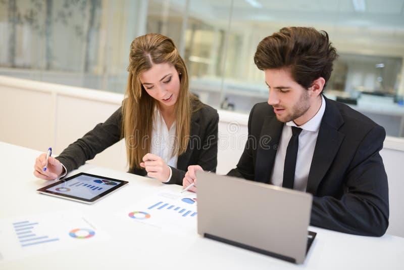 Affärsfolk som arbetar runt om tabellen i modernt kontor arkivbild