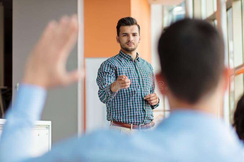 Affärsfolk som där upp lyfter handen på en konferens för att svara en fråga arkivfoto