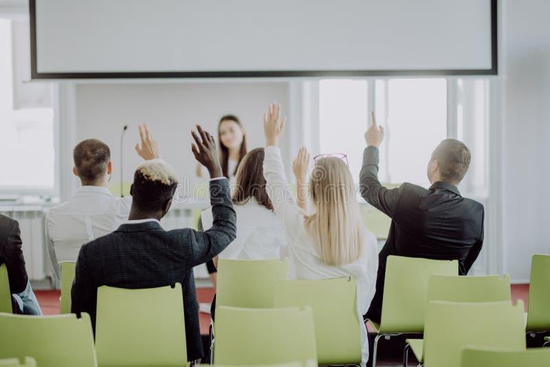Affärsfolk som där upp lyfter handen på en konferens för att svara en fråga Svar på frågor royaltyfri bild
