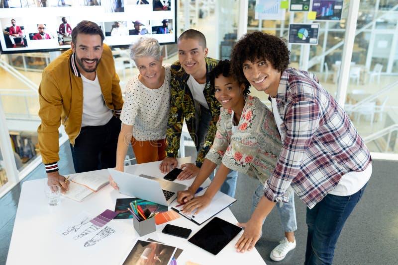 Affärsfolk som diskuterar över bärbara datorn i konferensrummet på kontoret royaltyfri bild