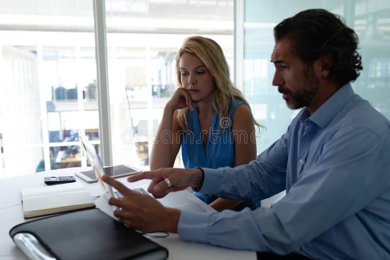 Affärsfolk som diskuterar över bärbara datorn på skrivbordet i ett modernt kontor royaltyfri fotografi