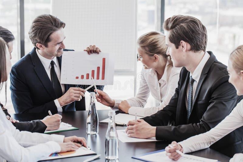 Affärsfolk som diskuterar diagram arkivfoto