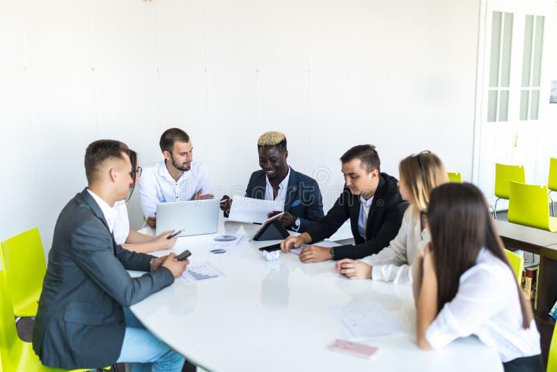 Affärsfolk som diskuterar diagrammen och graferna som visar resultaten av deras lyckade teamwork, mång- etnisk affär Affär arkivfoto