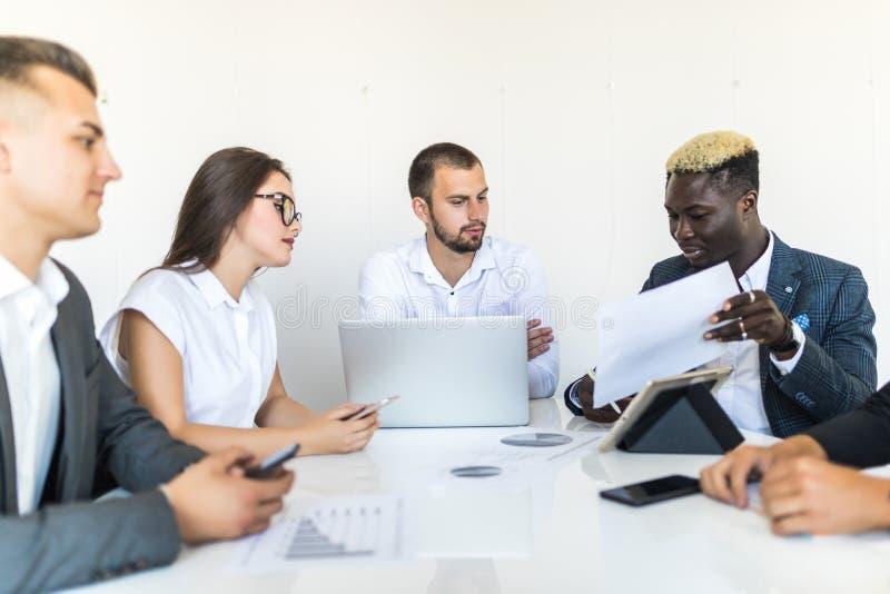Affärsfolk som diskuterar diagrammen och graferna som visar resultaten av deras lyckade teamwork, mång- etnisk affär Affär royaltyfria bilder