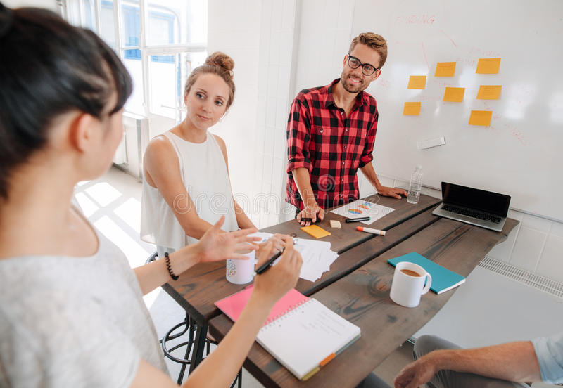 Affärsfolk som diskuterar i mötesrum på det idérika kontoret royaltyfria bilder