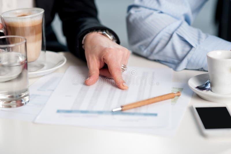 Affärsfolk som diskuterar månatlig statistik royaltyfria foton