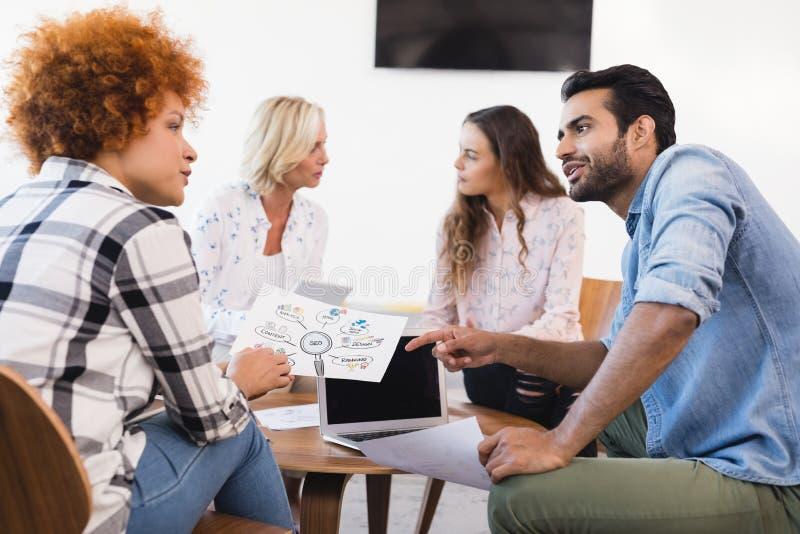 Affärsfolk som diskuterar, medan arbeta tillsammans royaltyfri fotografi