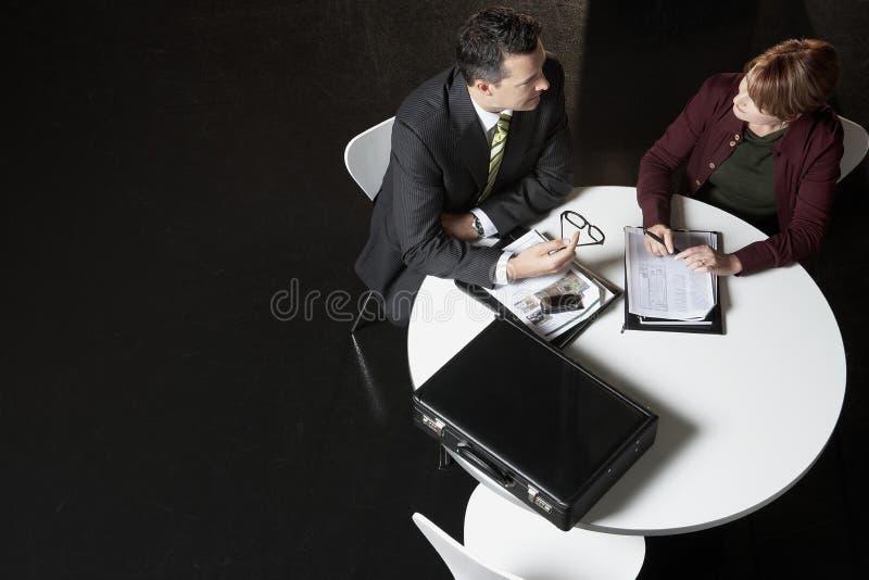 Affärsfolk som diskuterar skrivbordsarbete på skrivbordet royaltyfri bild