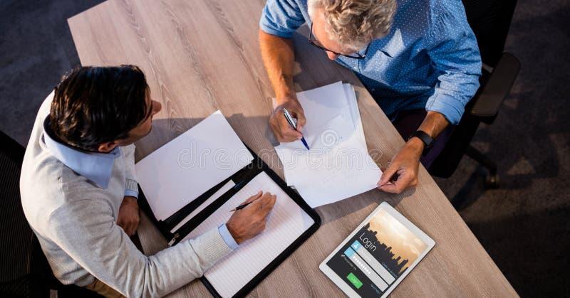 Affärsfolk som diskuterar vid signupskärmen på minnestavlaPC royaltyfri fotografi