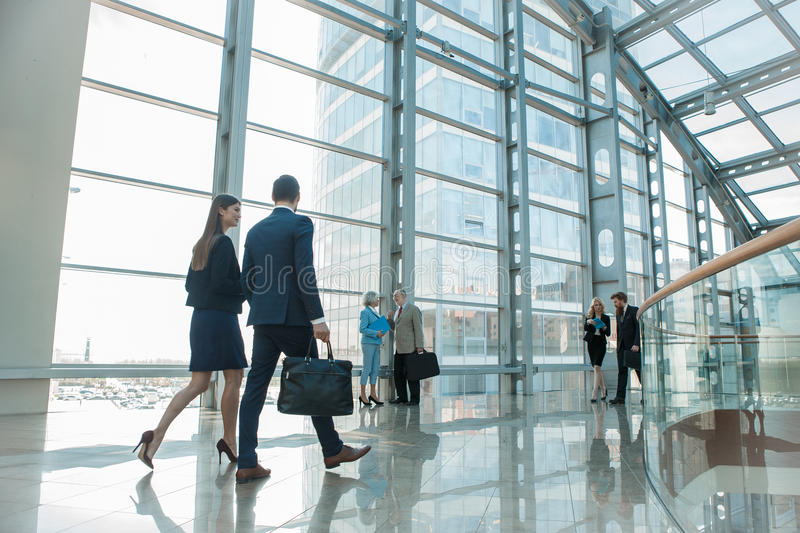Affärsfolk som går i glass byggnad arkivfoto