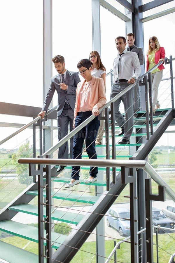 Affärsfolk som går ner trappa royaltyfria bilder