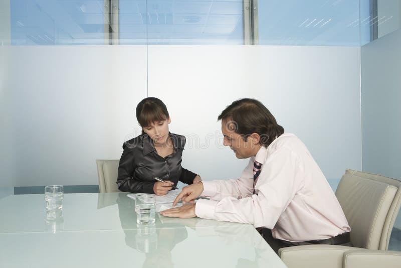 Affärsfolk som går till och med dokument i konferensrum arkivfoto