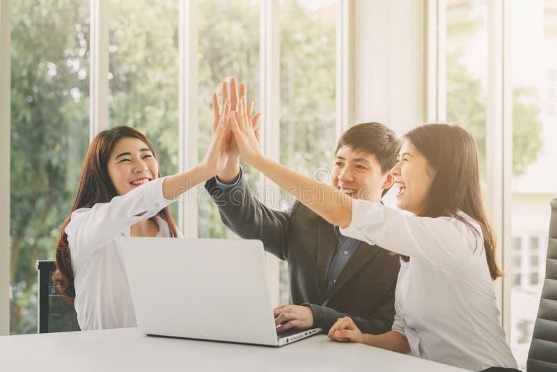 Affärsfolk som ger höjdpunkt fem för att fira framgång arkivfoton