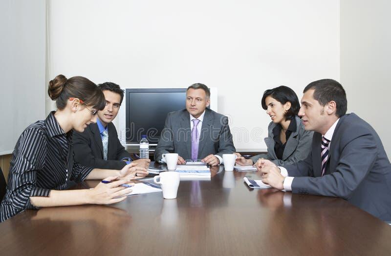 Affärsfolk som har diskussion i konferensrum arkivbild
