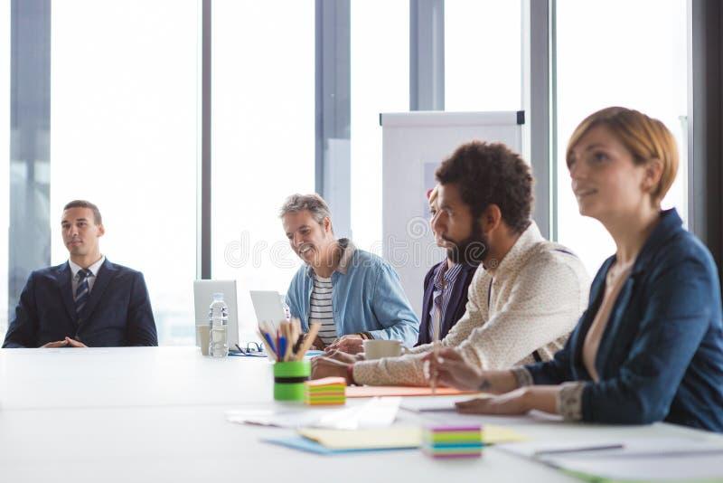Affärsfolk som har möte i modernt kontor arkivfoto