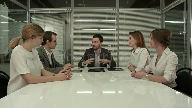 Affärsfolk som har styrelsemötet i modernt kontor arkivbilder