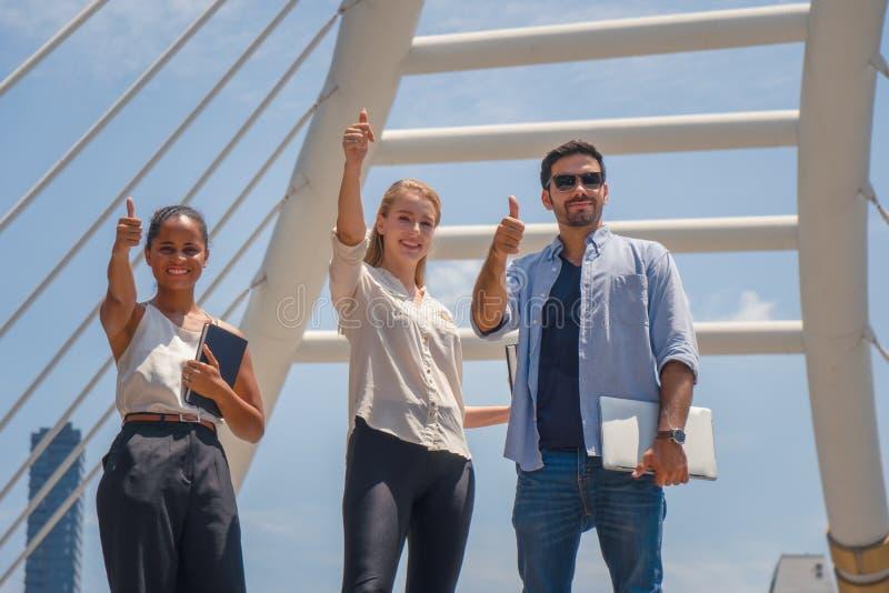 Affärsfolk som har tummen upp den utomhus- anden för tp-showlag av framgång tillsammans arkivbild