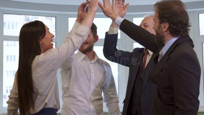 Affärsfolk som hihg-fiving på kontoret arkivbilder