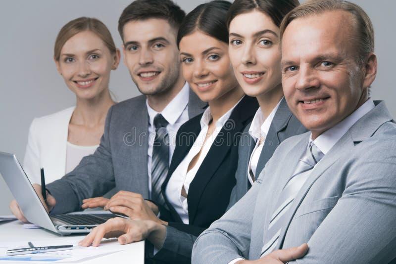 Affärsfolk som i rad sitter royaltyfri bild