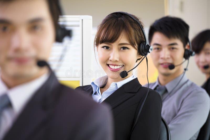 Affärsfolk som i regeringsställning arbetar med hörlurar med mikrofon arkivfoto