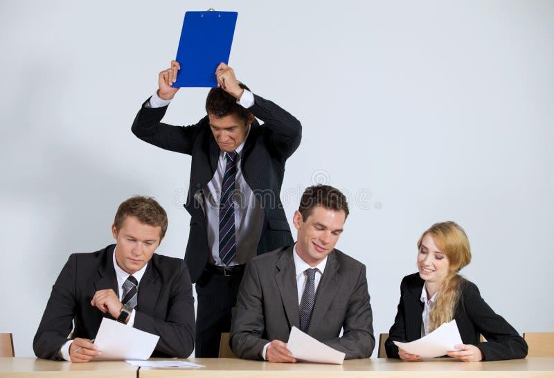 Affärsfolk som i regeringsställning arbetar medan frustrerad affärsman som kastar skrivplattan royaltyfri foto