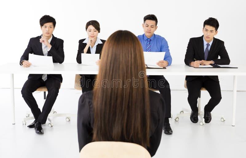 Affärsfolk som i regeringsställning intervjuar den unga affärskvinnan royaltyfri fotografi
