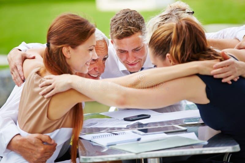 Affärsfolk som kramar för lagande royaltyfria bilder
