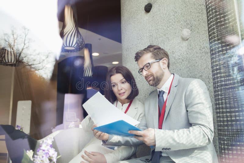 Download Affärsfolk Som Läser Dokumentet, Medan Sitta I Konventcentrum Arkivfoto - Bild av sakkunskap, möte: 78726782