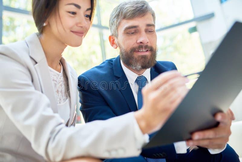 Affärsfolk som läser dokumentet på skrivplattan fotografering för bildbyråer