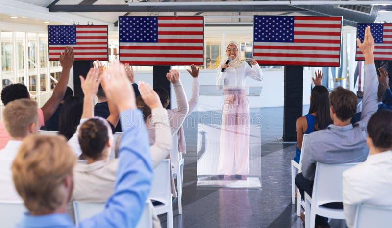 Affärsfolk som lyfter deras händer, medan delta i affärsseminarium i konferensmöte arkivfoton