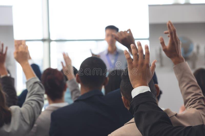 Affärsfolk som lyfter händer i ett affärsseminarium arkivfoton