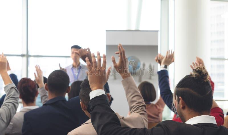 Affärsfolk som lyfter händer på ett affärsseminarium royaltyfri fotografi