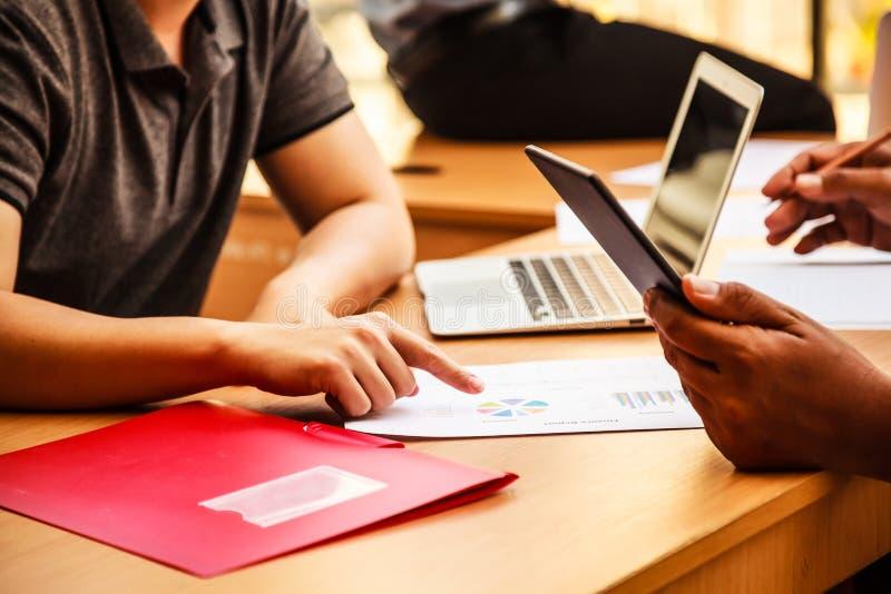 Affärsfolk som möter i kontorsbegreppet, genom att använda idéer, diagram, datorer, minnestavla, smarta apparater på affärsplanlä arkivfoton