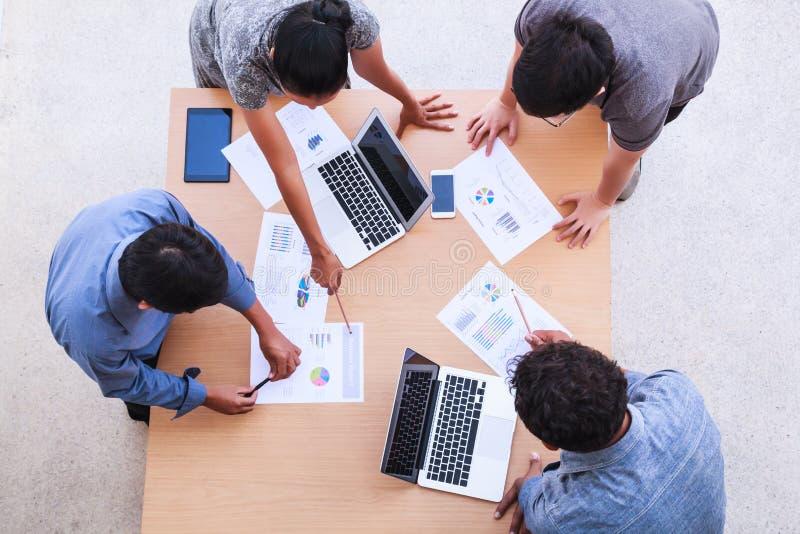 Affärsfolk som möter i kontorsbegreppet, genom att använda idéer, diagram, datorer, minnestavla, smarta apparater på affärsplanlä arkivbild