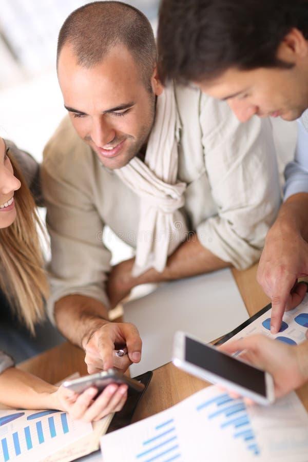 Affärsfolk som möter och använder smartphones arkivfoton