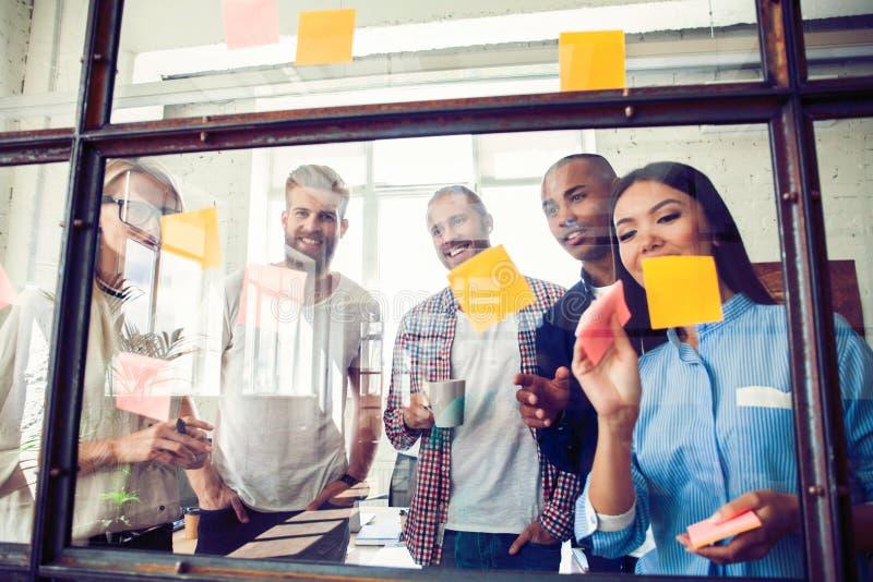 Affärsfolk som möter på kontoret och bruksstolpen som den noterar för att dela idé Hjärna och exponeringar Klibbig anmärkning på  arkivbild