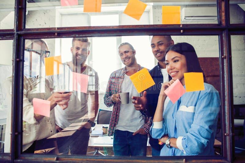 Affärsfolk som möter på kontoret och bruksstolpen som den noterar för att dela idé Hjärna och exponeringar Klibbig anmärkning på  arkivfoto
