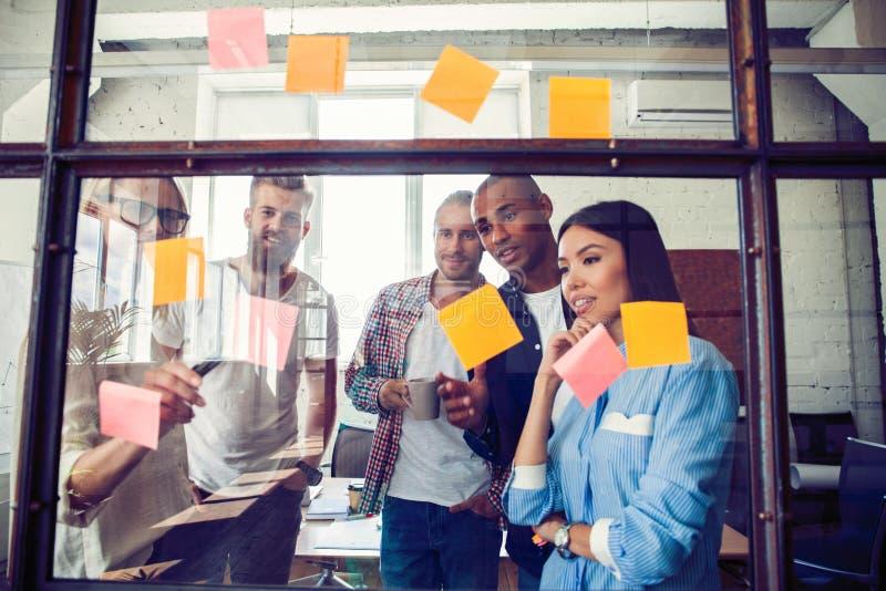 Affärsfolk som möter på kontoret och bruksstolpen som den noterar för att dela idé Hjärna och exponeringar Klibbig anmärkning på  royaltyfri foto