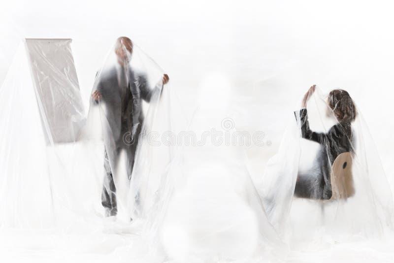 Affärsfolk som möts samtidigt som de är täckta med plast för att skydda sig mot Coronavirus arkivfoto