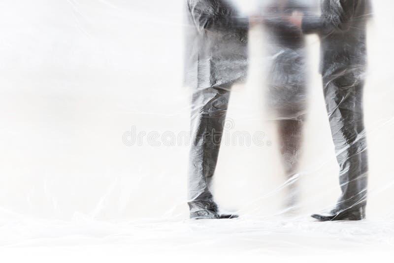 Affärsfolk som möts samtidigt som de är täckta med plast för att skydda sig mot Coronavirus arkivfoton