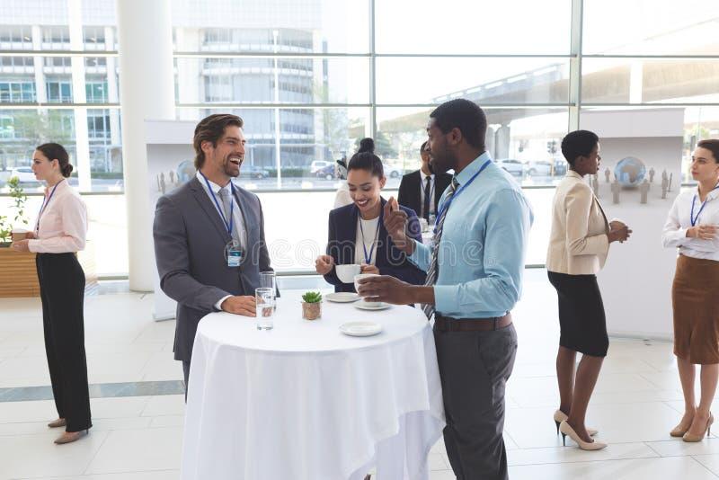 Affärsfolk som påverkar varandra med de på tabellen under ett seminarium arkivfoton