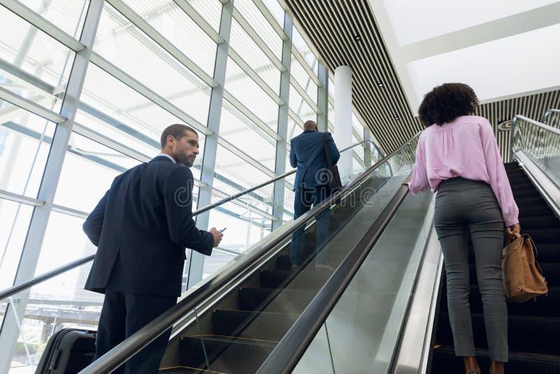 Affärsfolk som reser upp en rulltrappa royaltyfria foton