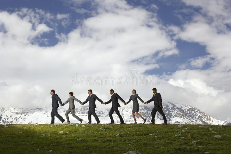 Affärsfolk som rymmer händer och går till och med berg arkivfoto