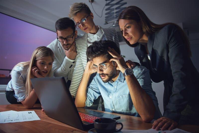 Affärsfolk som sent tillsammans arbetar som ett lag arkivbild
