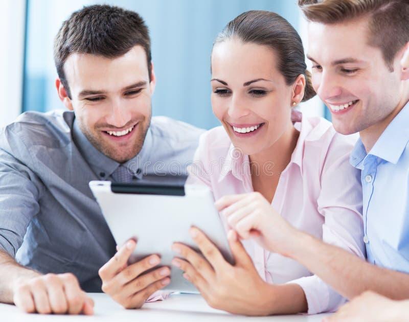 Affärsfolk som ser den digitala minnestavlan royaltyfri foto