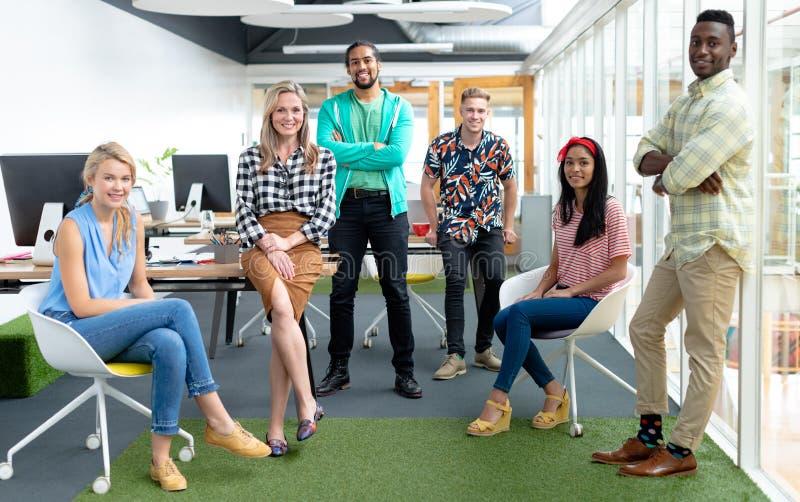 Affärsfolk som ser kameran i ett modernt kontor arkivfoton