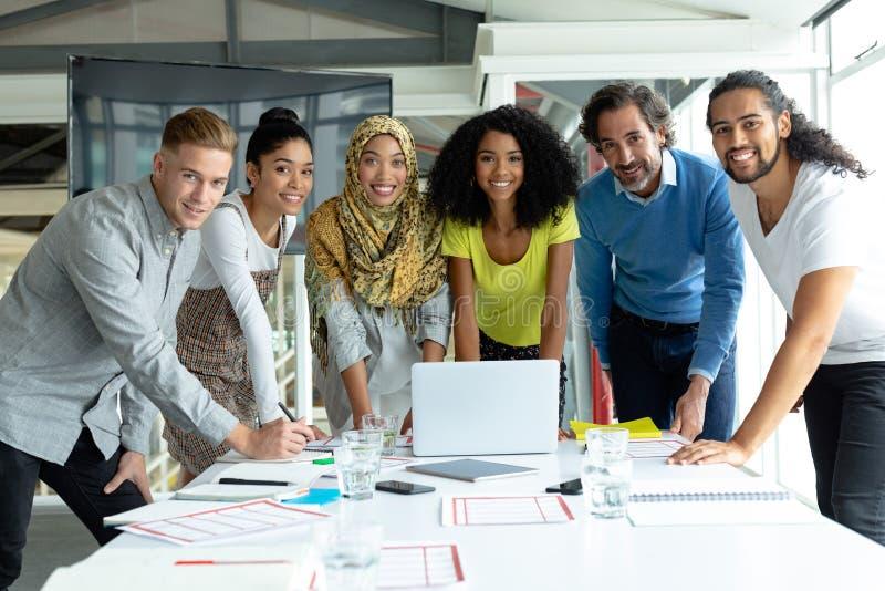 Affärsfolk som ser kameran, medan arbeta tillsammans på konferensrum i ett modernt kontor arkivbilder