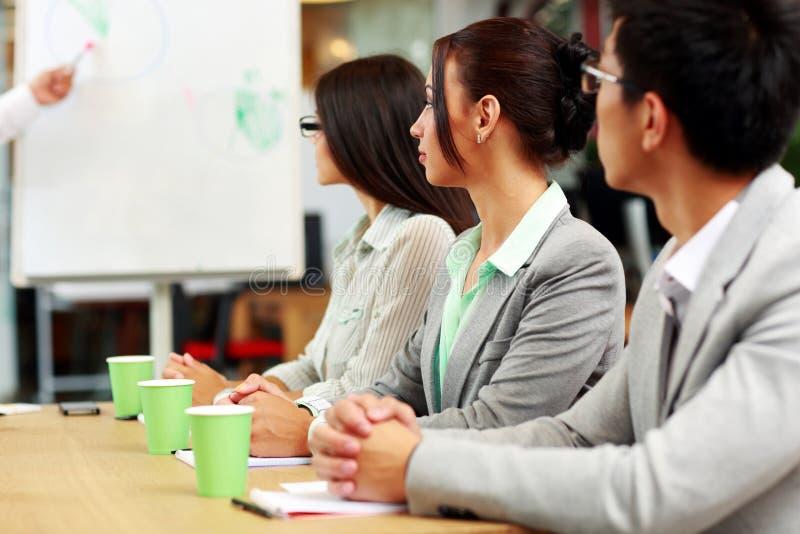 Affärsfolk som sitter runt om en tabell under ett möte royaltyfri foto